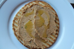 Spread a nice layer of highmade hummus on top of pita. Drizzle additional garlic oil over the hummus.