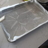 "Spray pan with non-stick. It acts as ""glue"" for the parchment paper."